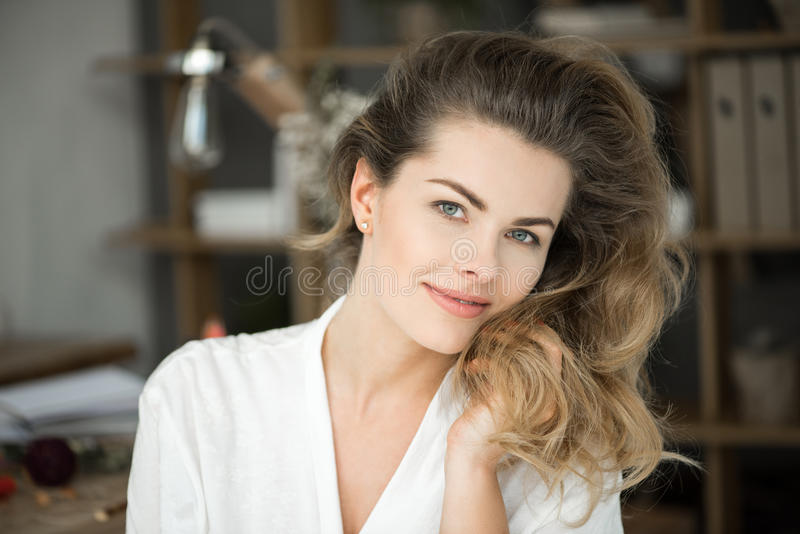 Happy tender blonde woman in white clothes smiling at camera royalty free stock photos