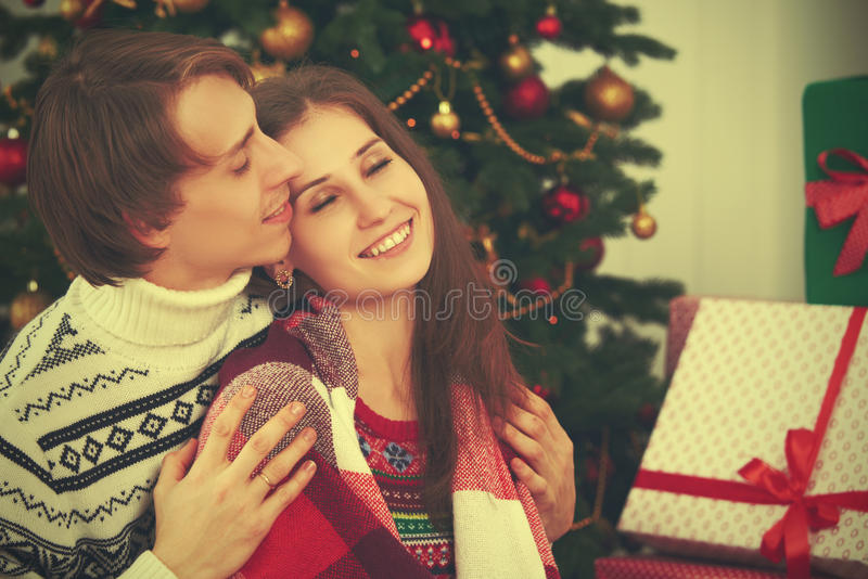 Happy tender loving couple in embrace warmed at Christmas tree. Happy tender loving couple in an embrace warmed at Christmas tree royalty free stock photography
