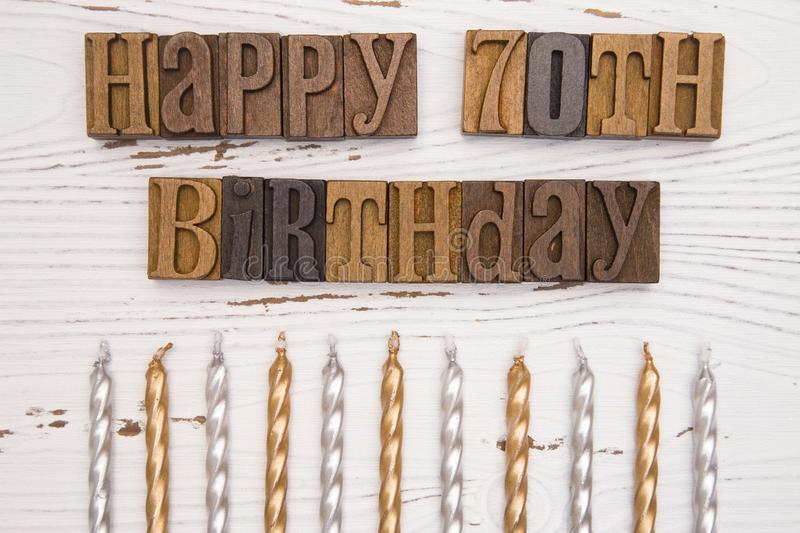 Happy 70th Birthday Spelled in Type Set. On a distressed wooden table royalty free stock images