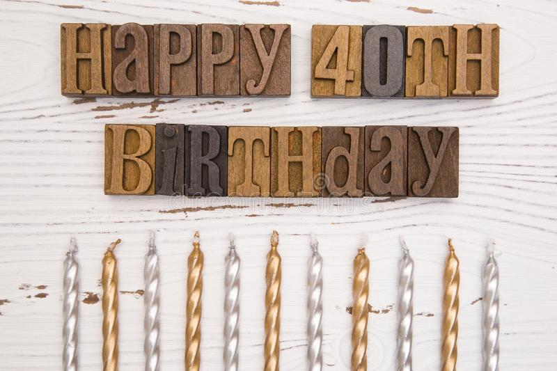 Happy 40th Birthday Spelled in Type Set. On a distressed wooden table stock photography