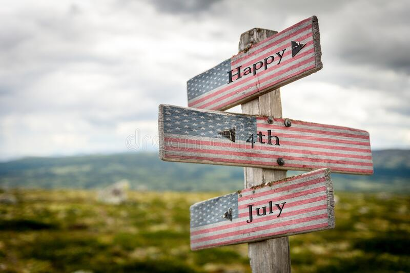 Happy 4th of july text on wooden american flag signpost outdoors. In nature royalty free stock photos