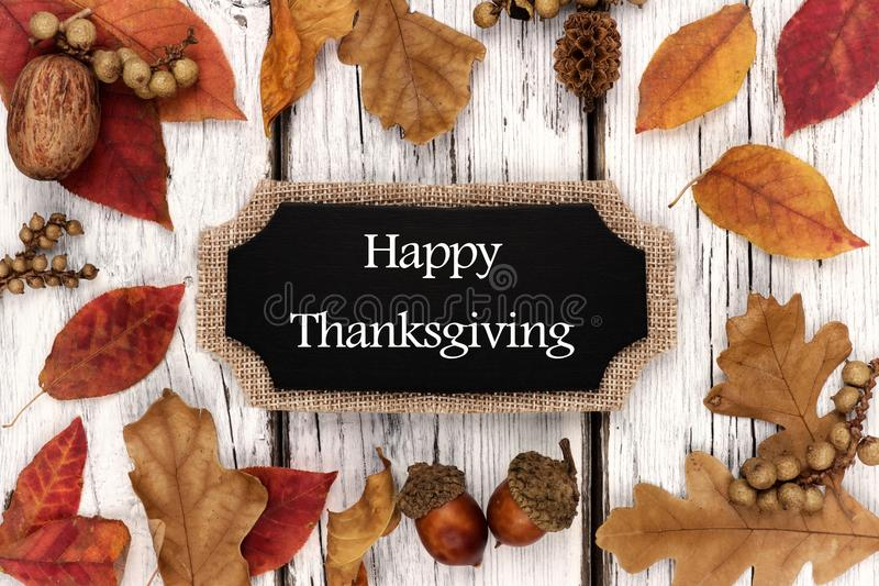 Happy Thanksgiving chalkboard tag with leaves over white wood. Happy Thanksgiving chalkboard tag with frame of autumn leaves over a white wood background royalty free stock image