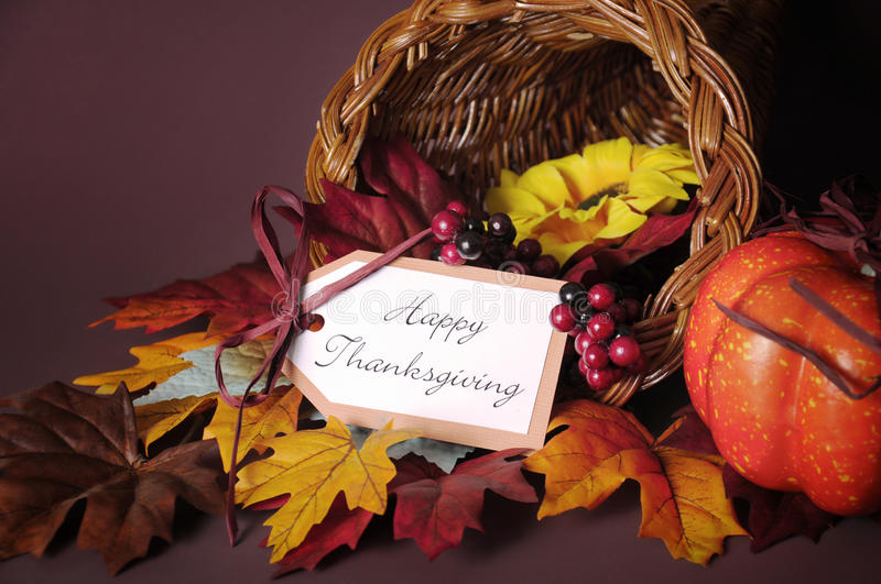 Happy Thanksgiving cornucopia wicker basket closeup. Happy Thanksgiving cornucopia wicker basket with autumn leaves, pumpkin and greeting tag on candlelit