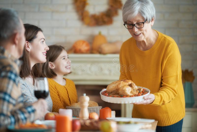 Happy Thanksgiving Day. ! Autumn feast. Family sitting at the table and celebrating holiday. Grandparents, mother and child. Traditional dinner stock image