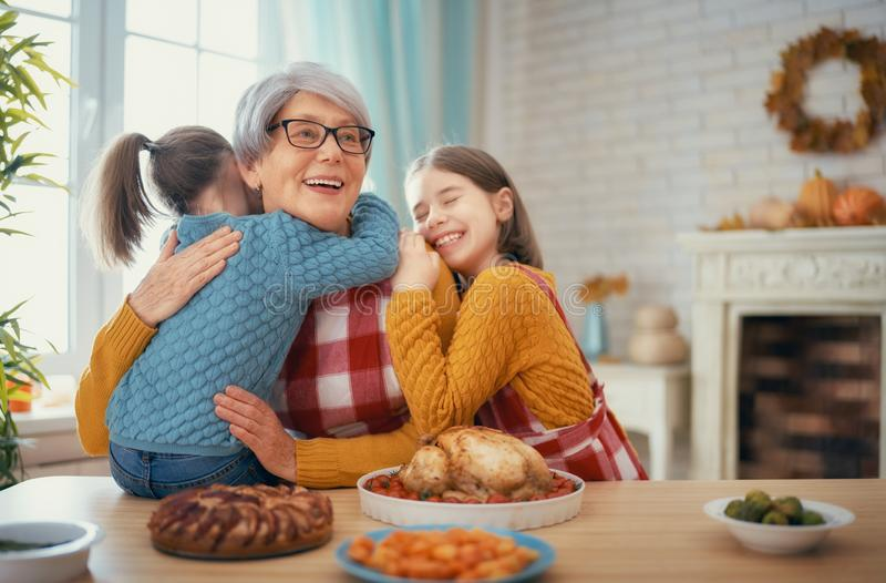 Happy Thanksgiving Day. ! Autumn feast. Family sitting at the table and celebrating holiday. Traditional dinner. Grandmother and granddaughters royalty free stock photo