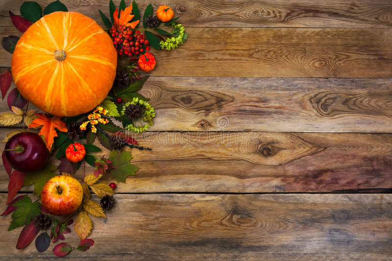 Happy Thanksgiving decor with fall leaves on wooden background. Happy Thanksgiving decor with pumpkin, apples and autumn leaves on the left side of rustic wooden royalty free stock image