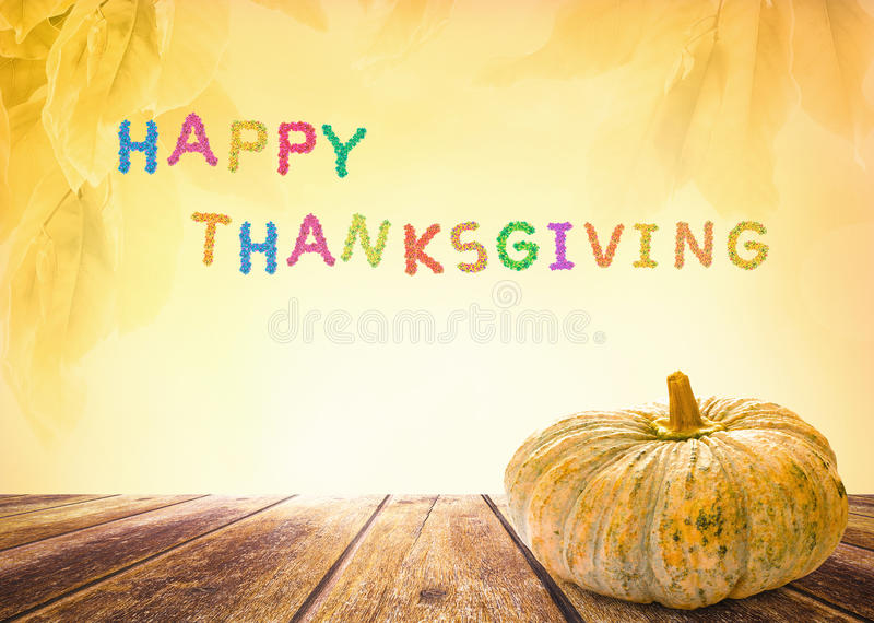 HAPPY THANKSGIVING. Fruitful text for HAPPY THANKSGIVING and autumn still life with pumpkin on a wooden surface royalty free stock photos