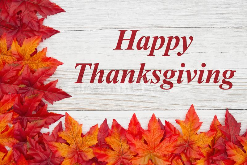 Happy Thanksgiving greeting with red and orange fall leaves on weathered wood. Happy Thanksgiving greeting with red and orange fall leaves on weathered whitewash royalty free stock images