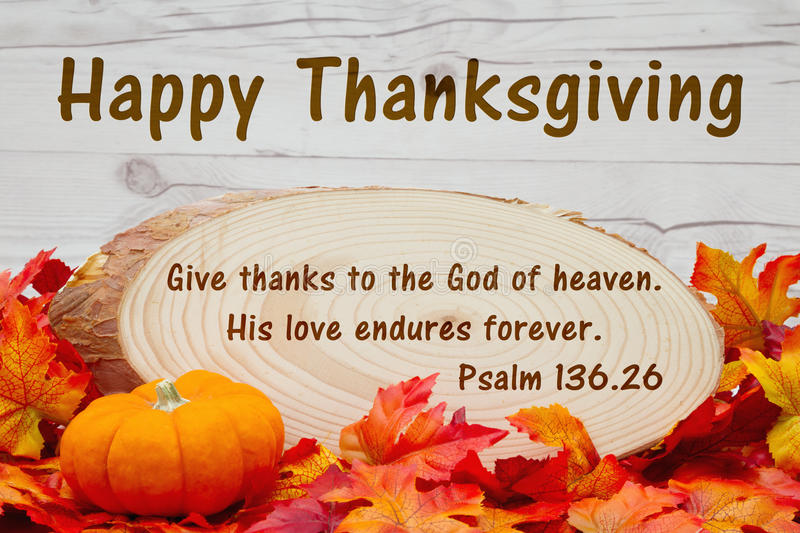 Happy Thanksgiving message. Some fall leaves, an alarm clock and wood plaque on weathered wood with text Psalm 136 stock photo