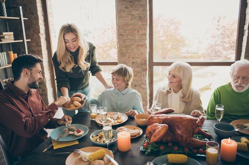 Happy thanksgiving. Photo of big family gathering sit feast meals dinner table wife giving everybody fresh baked bread. Happy thanksgiving. Photo of big family royalty free stock photography