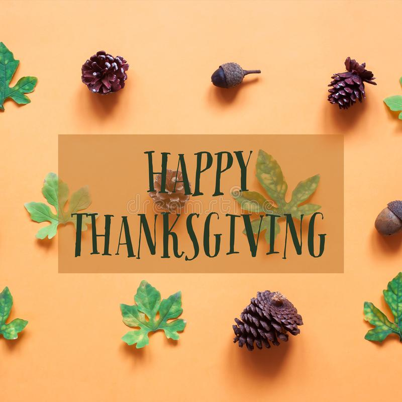 Happy Thanksgiving text with pine cones and leaves stock image