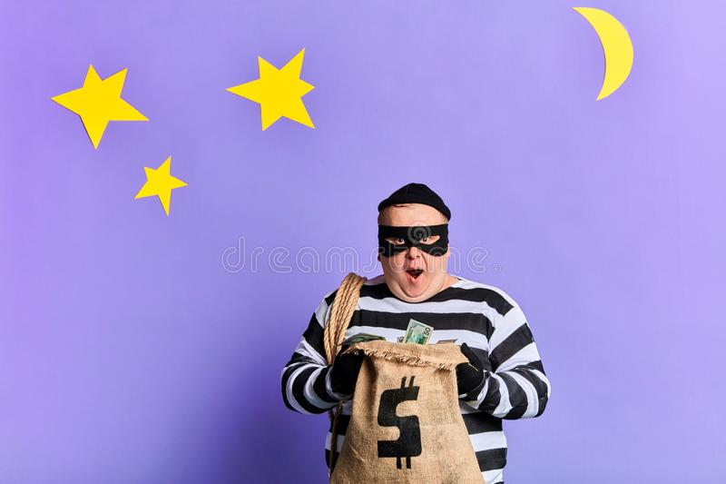 Happy thief in mask and gloves opening a sack of money stock images