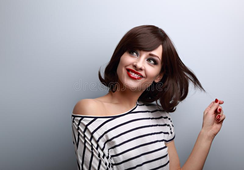 Happy thinking flirting young woman with short hairstyle lookin stock image