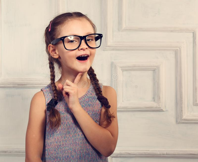Happy thinking kid girl in fashion glasses with excited emotional face looking on studio background. Closeup toned portrait stock photos