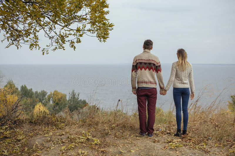 Happy thoughtful couple standing on a cliff near sea hugging each other in cold foggy cloudy autumn weather. Copy space stock photos