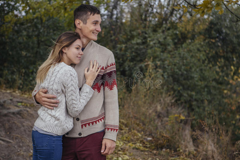 Happy thoughtful couple standing on a cliff near sea hugging each other in cold foggy cloudy autumn weather. Copy space royalty free stock images