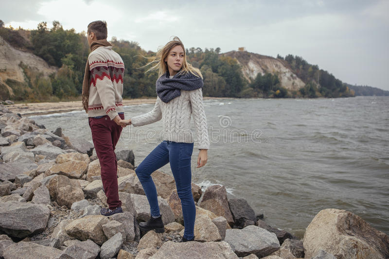Happy thoughtful couple standing on a rock beach near sea hugging each other in cold foggy cloudy autumn weather. Copy space royalty free stock image