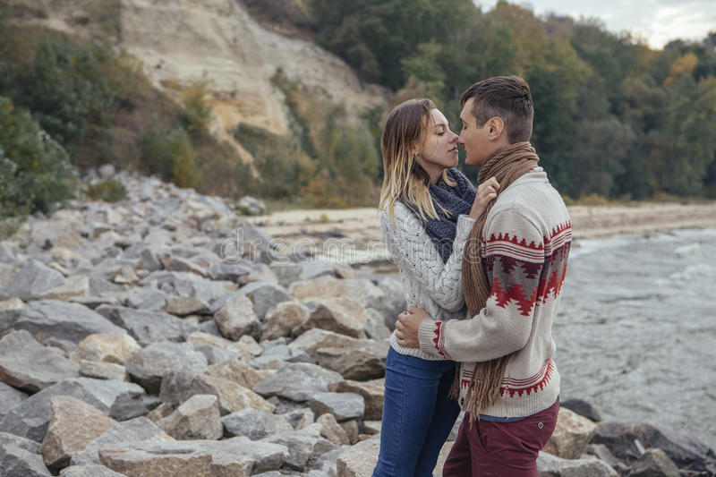 Happy thoughtful couple standing on a rock beach near sea hugging each other in cold foggy cloudy autumn weather. Copy space stock photo