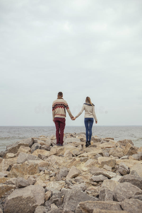 Happy thoughtful couple standing on a rock beach near sea hugging each other in cold foggy cloudy autumn weather. Copy space royalty free stock photo