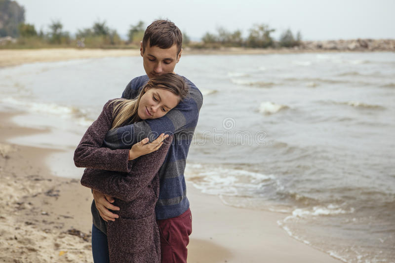 Happy thoughtful couple standing on a rock beach near sea hugging each other in cold foggy cloudy autumn weather. Copy space royalty free stock photos