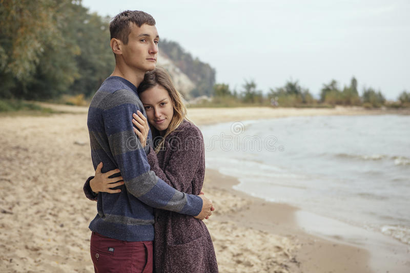 Happy thoughtful couple standing on a rock beach near sea hugging each other in cold foggy cloudy autumn weather. Copy space royalty free stock images