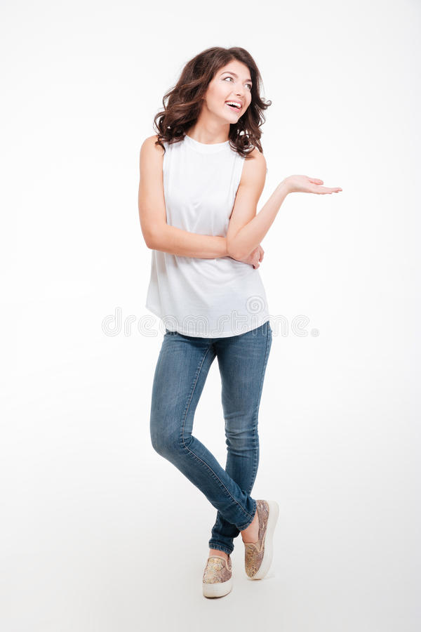 Happy thoughtful woman holding copyspace on the palm. Full length portrait of a happy thoughtful woman holding copyspace on the palm isolated on a white stock photography