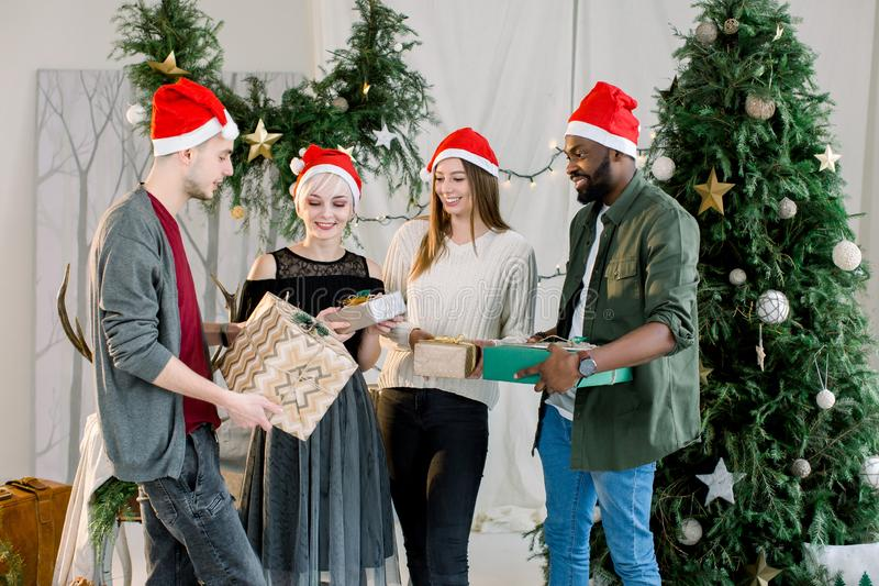 Happy three Caucasian women, Caucasian man and African man holding Christmas presents at home. Christmas tree royalty free stock photo