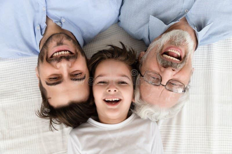 Happy three generation family lying in row, portrait, closeup view. Happy multi 3 three generation family lying in row looking at camera, smiling child boy son stock photography