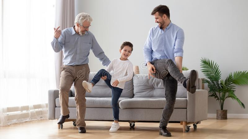Happy three generation men family dancing together in living room. Happy active 3 three generation men family senior old grandfather, young adult dad and cute stock image