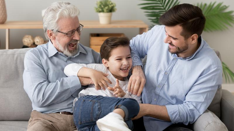 Happy three generation men family playing laughing tickling on sofa. Happy funny multi three 3 generation men family old senior grandfather, young grown son royalty free stock image
