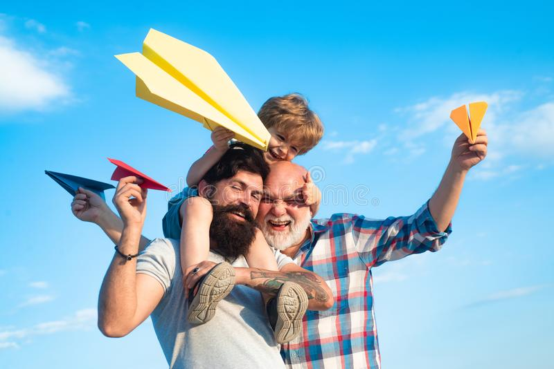 Happy three generations of men have fun and smiling on blue sky background. Enjoy family together. Dream of flying. Kids royalty free stock photography