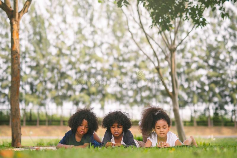 Happy three little friends laying on the grass in the park. american african children playing toy in park. stock photos