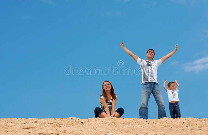 Happy three on sand dune top. Happy young family of three on top of sand dune with blue-blue sky on background royalty free stock images