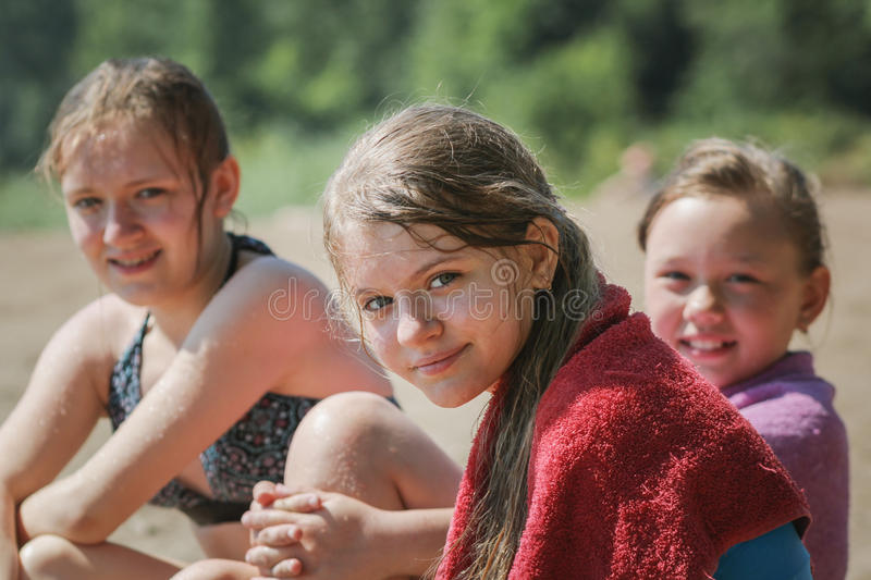 Happy three teen friends girls on beach after swimming royalty free stock image