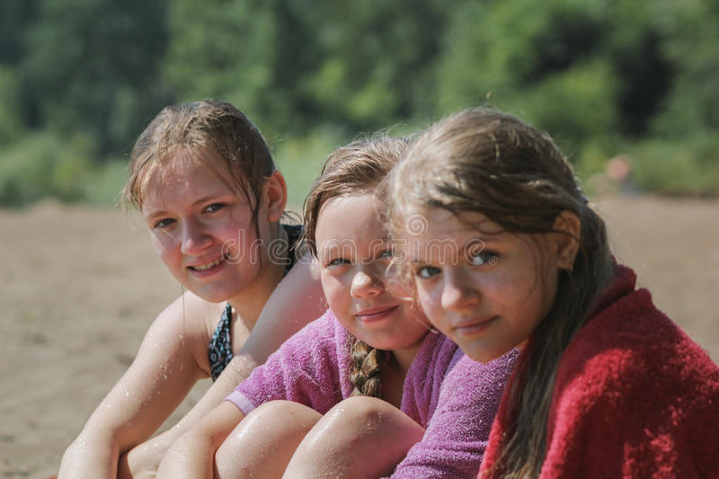 Happy three teen girlfriends on the beach after river swimming stock image