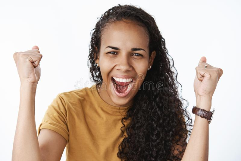Happy and thrilled delighted african american girl with curly hair raising clenched fists in cheer and success yelling. Yeah and squinting joyfully receiving royalty free stock photo