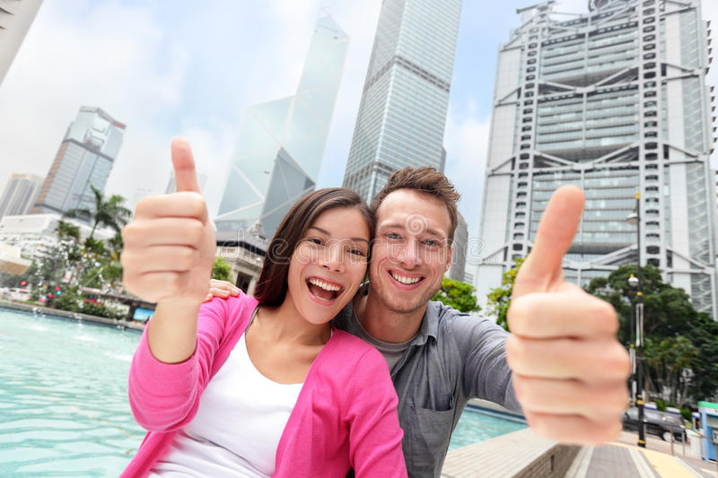 Happy thumbs up multicultural couple in Hong Kong royalty free stock image