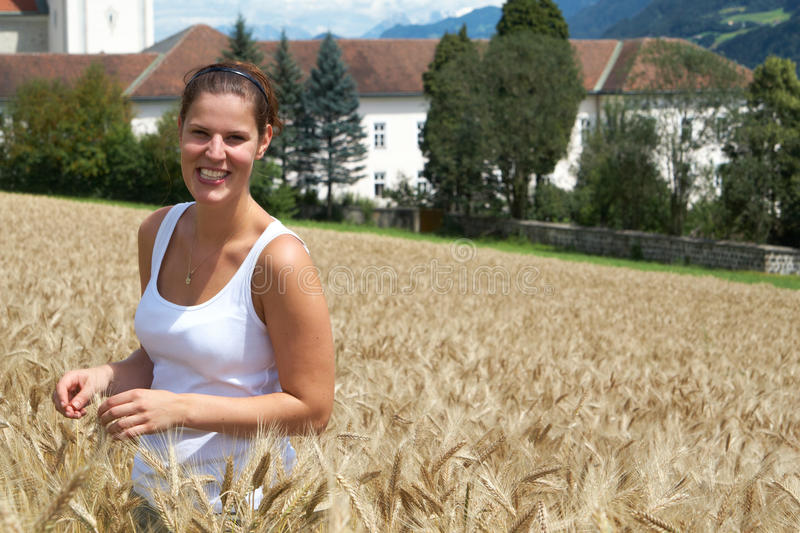 Happy times. A young woman in the yellow field under blue sky in a rural alpine setting. Village in the background. Focus is on the woman stock photos