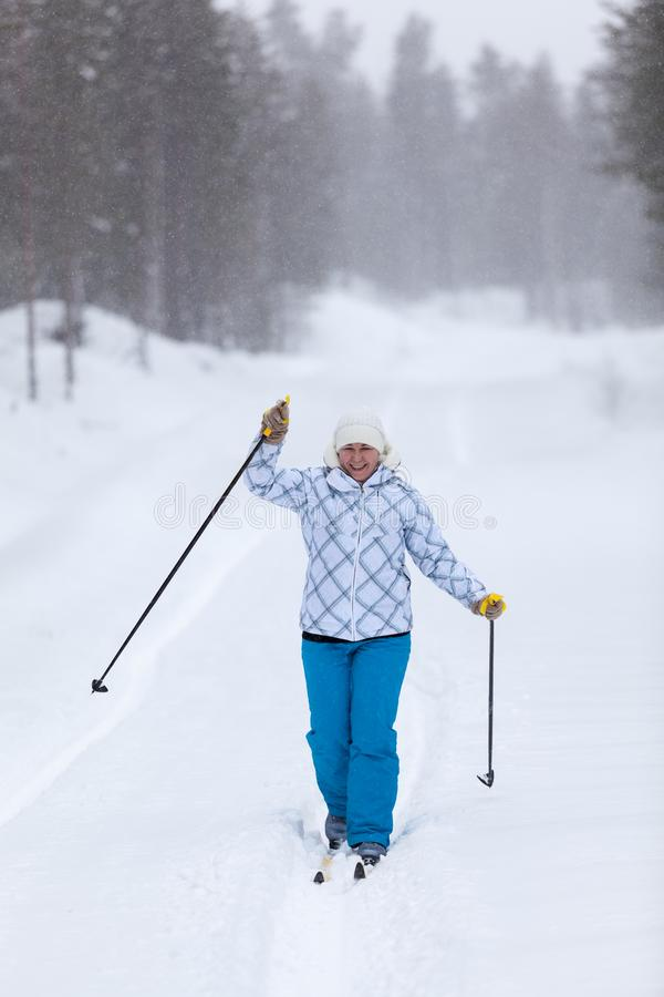 Happy and tired woman running on ski on forest road at strong blizzard and greeting with poles royalty free stock photos