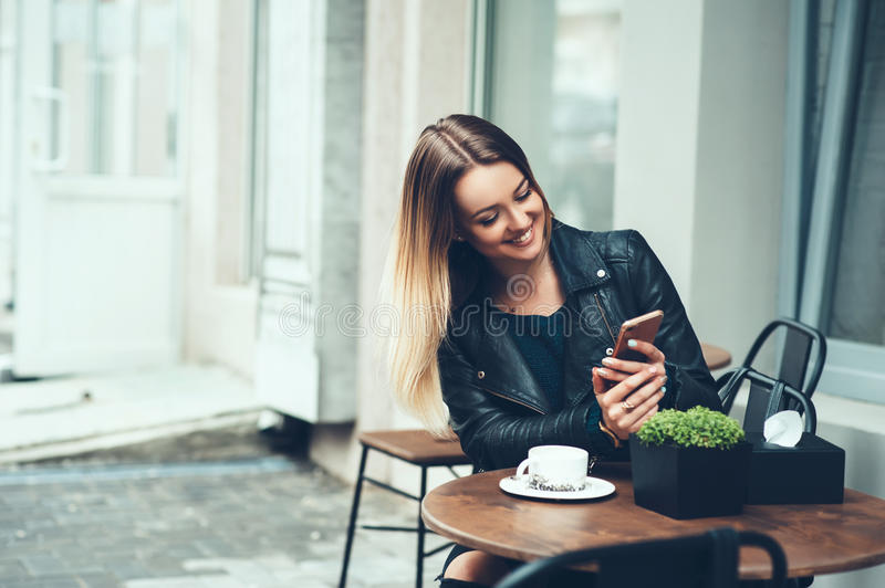 Always happy to communicate with friends. Beautiful young woman sitting in cafe typing message to her friend while drinking taste. Coffee and smiling. Little stock images