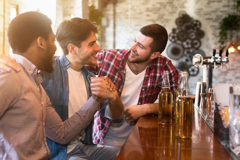 Happy to finally meet old friends in bar stock images