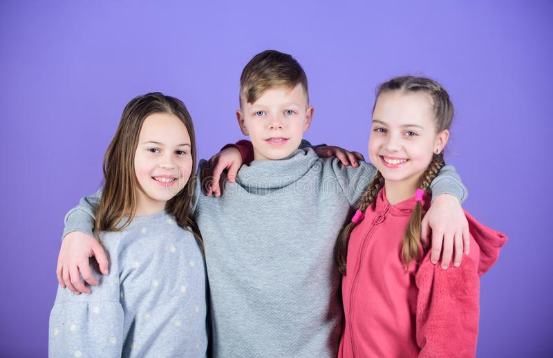 Happy to have such good friends. Teens friends. Girl and boy true friendship. Children smiling faces on violet. Background. Friends hug. Cheerful youth royalty free stock photos