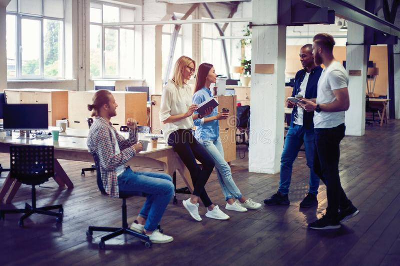 Happy to work together. Group of young business people communicating while working in the office. Happy to work together. Group of young business people royalty free stock photo