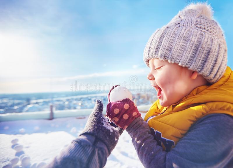Happy toddler baby boy playing snowballs with family at sunny winter day. Delighted toddler baby boy playing snowballs with family at sunny winter day royalty free stock image