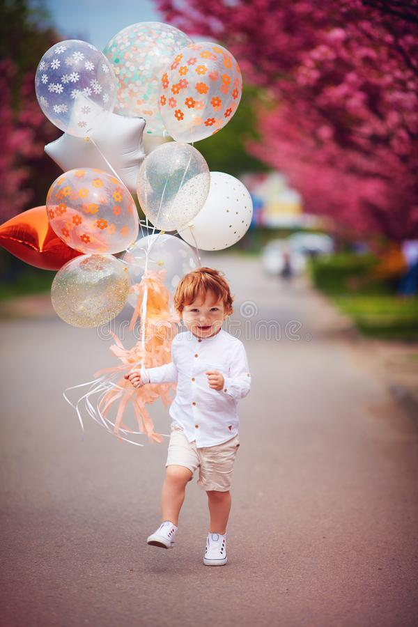 Happy toddler boy running the spring street with the bunch of air balloons stock photos