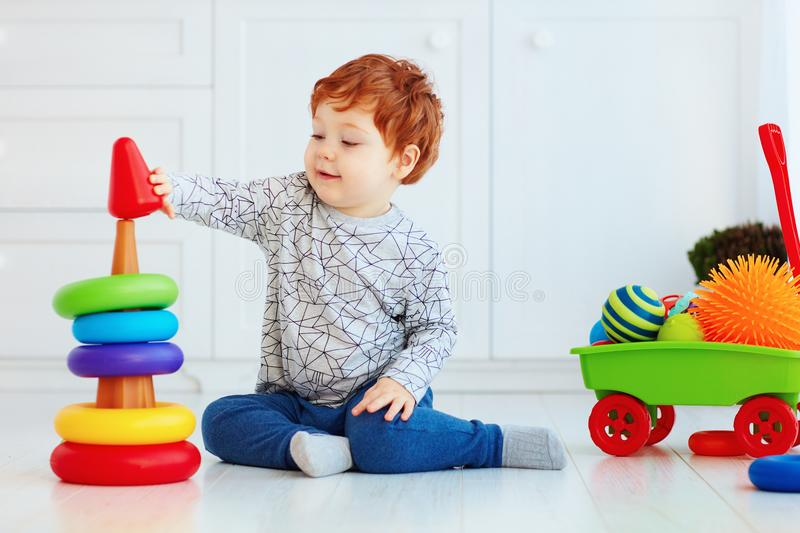 Happy toddler baby boy sorting colorful rings on pyramid royalty free stock image