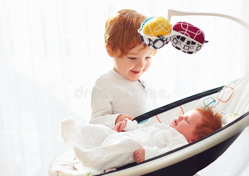 Happy toddler baby brother welcoming his little baby sister, that lying in cradle swings. Happy toddler baby brother is welcoming his little baby sister, that royalty free stock photos