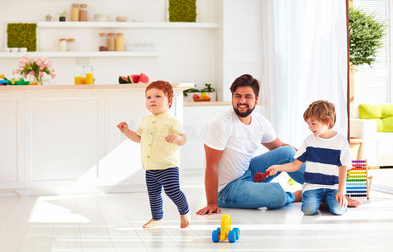 Happy toddler baby playing with father and brother at home at sunny summer day stock photos