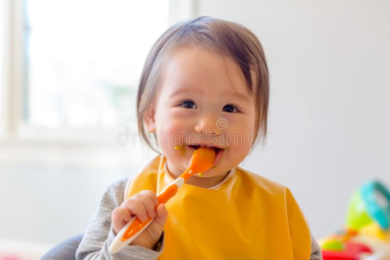 Happy toddler boy eating a meal royalty free stock photography