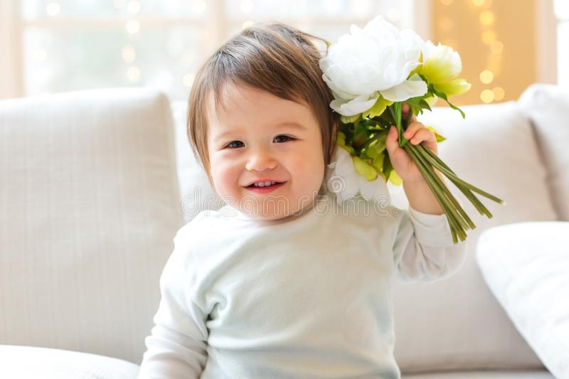 Happy toddler boy playing with flowers royalty free stock photos